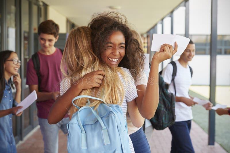 Två flickor som firar examenresultat i skolakorridor royaltyfria bilder