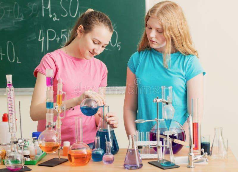 Två flickor som gör kemikalieexperiment royaltyfria bilder