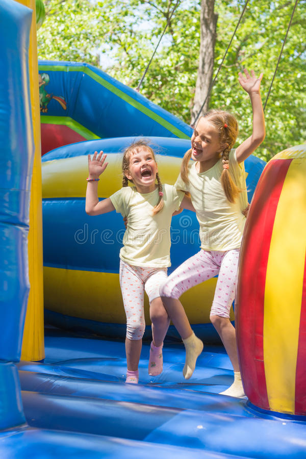 Två flickor som grimacing hoppa lyckligt på den uppblåsbara trampolinen royaltyfri bild
