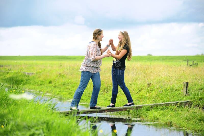Två flickor som har gyckel på vattnet arkivfoto