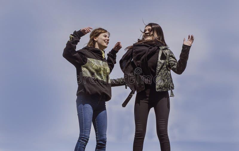 Två flickor som hoppar mot den blåa himlen royaltyfri bild