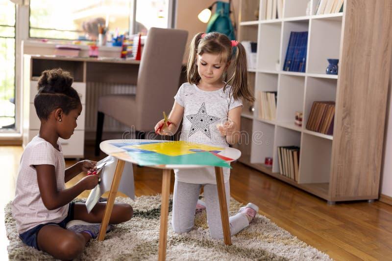 Två flickor som klipper färgrikt papper royaltyfri bild