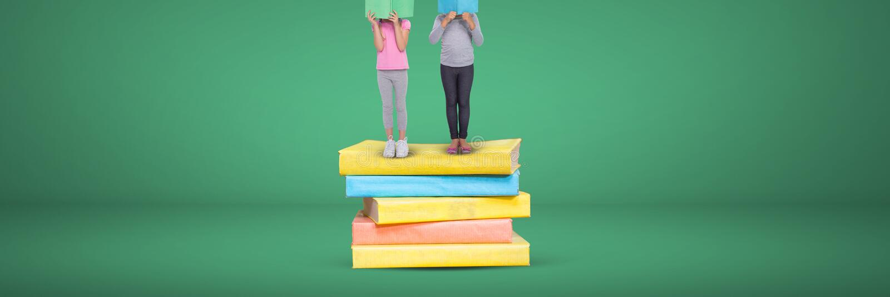 Två flickor som läser och står på en hög av böcker med grön bakgrund royaltyfri bild