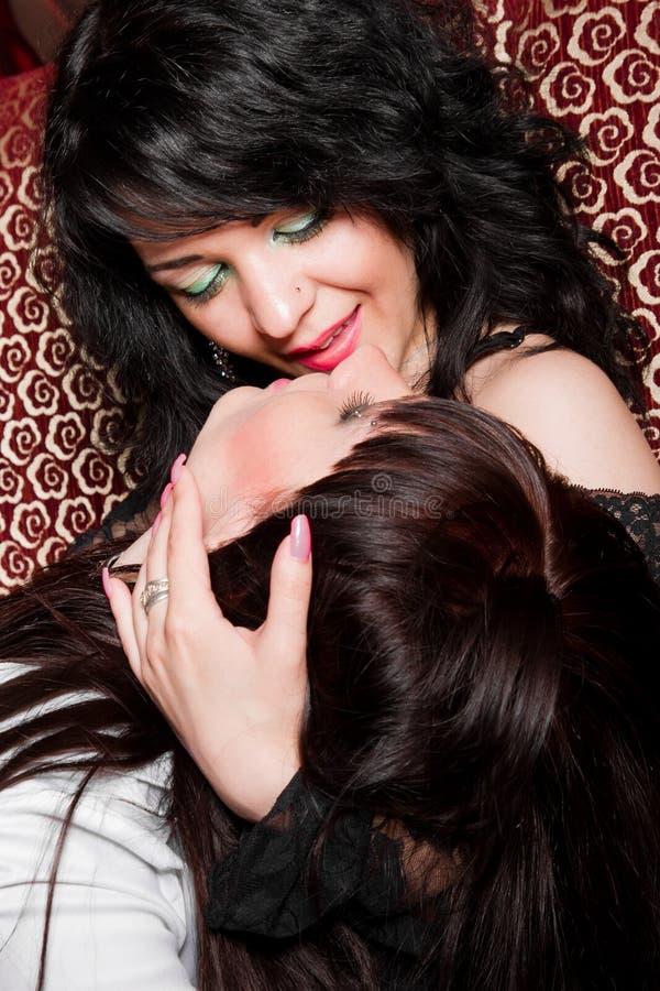 Två flickor som leker lesbisk kvinna i nattklubb royaltyfri foto