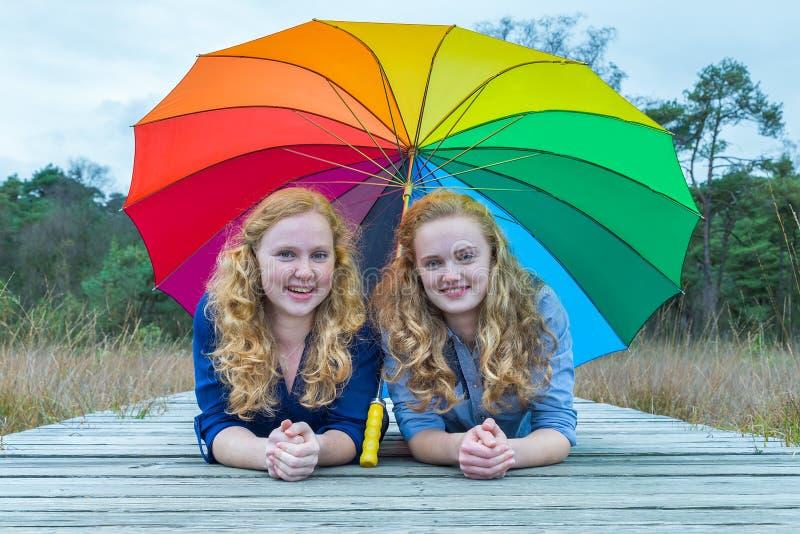 Två flickor som ligger i natur under det färgrika paraplyet royaltyfri bild