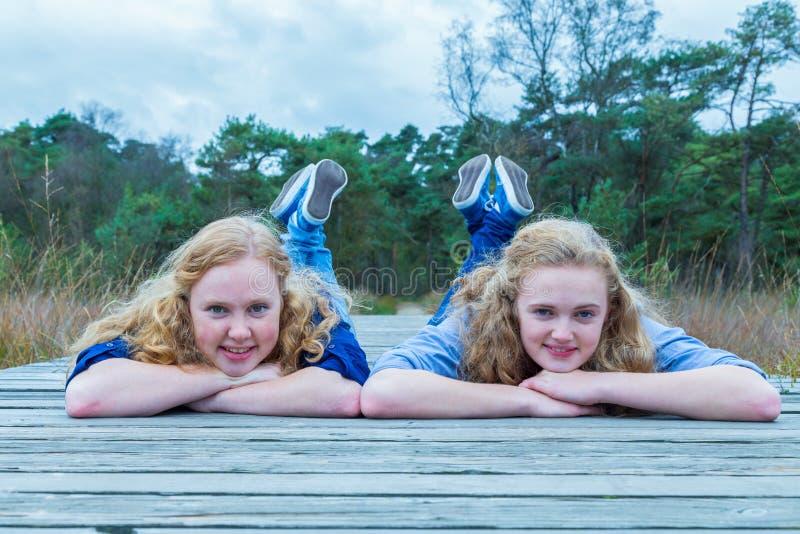 Två flickor som ligger på träbanan i natur arkivbilder