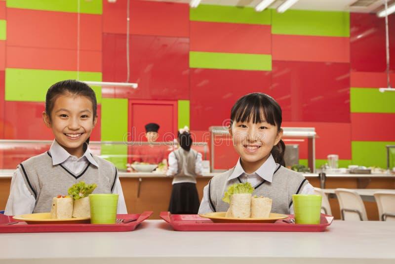 Två flickor som sitter i skolakafeteria fotografering för bildbyråer