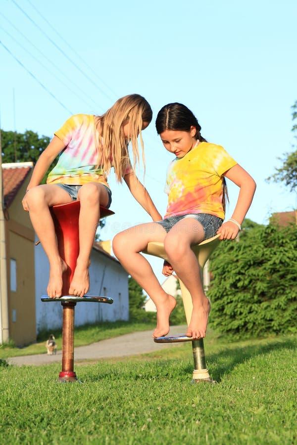 Två flickor som sitter på stångstolar arkivfoto