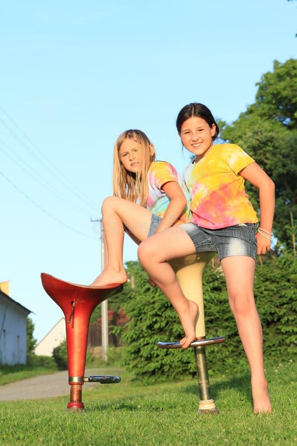 Två flickor som sitter på stångstolar arkivbild