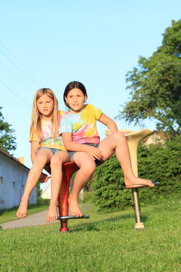 Två flickor som sitter på stångstolar royaltyfria foton