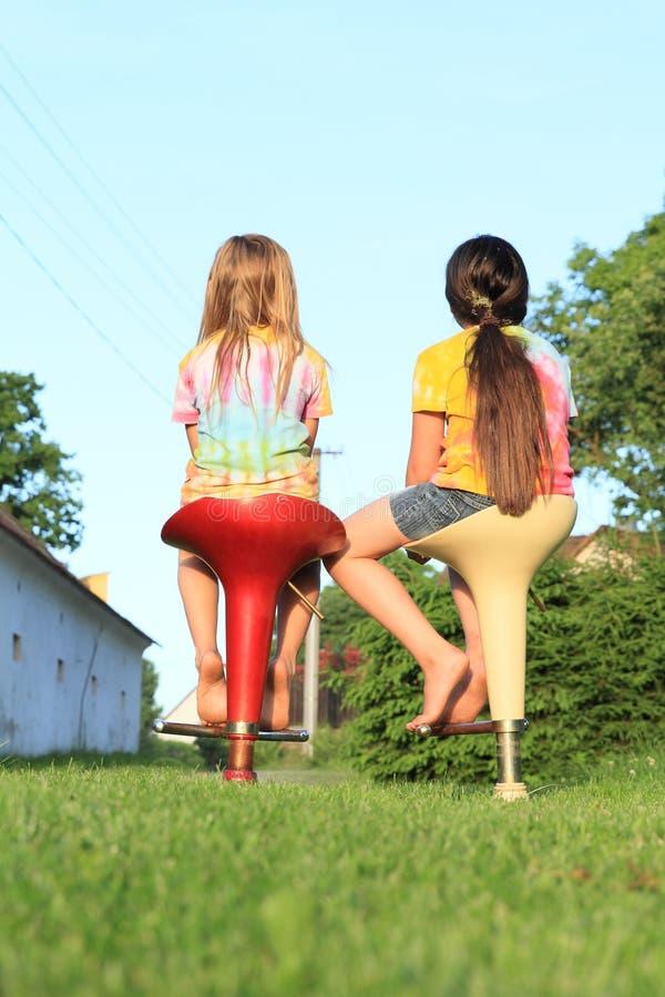 Två flickor som sitter på stångstolar arkivbilder