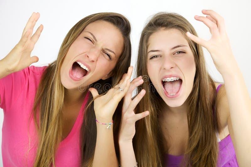 Två flickor som skriker som den isolerade galna seende kameran arkivbild