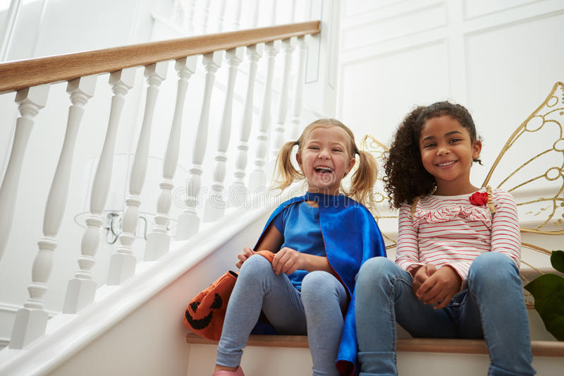 Två flickor som spelar att klä upp, spelar sammanträde på trappa arkivfoto