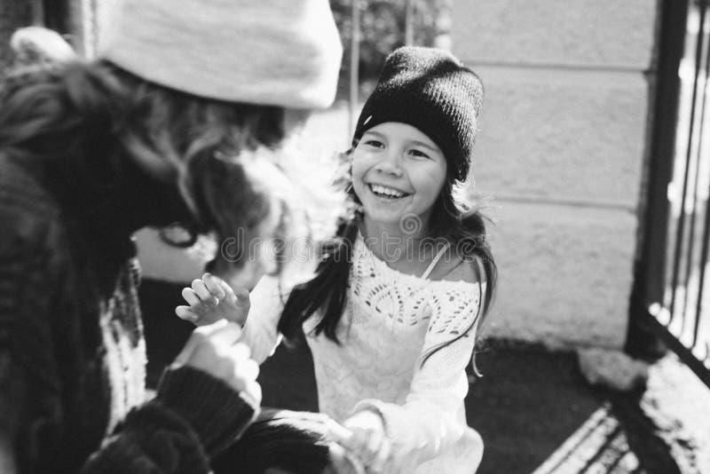 Två flickor som spelar i gatan tillsammans royaltyfri foto