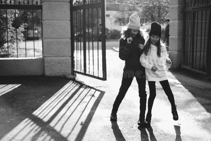 Två flickor som spelar i gatan tillsammans fotografering för bildbyråer