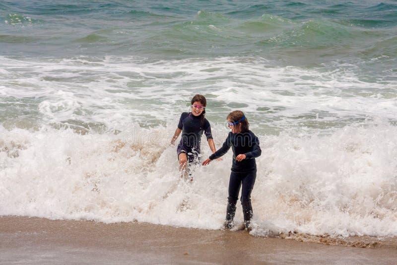 Två flickor som spelar i havvågor arkivbilder