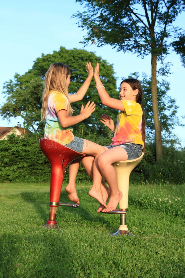 Två flickor som spelar leken, medan sitta på stångstolar royaltyfri fotografi