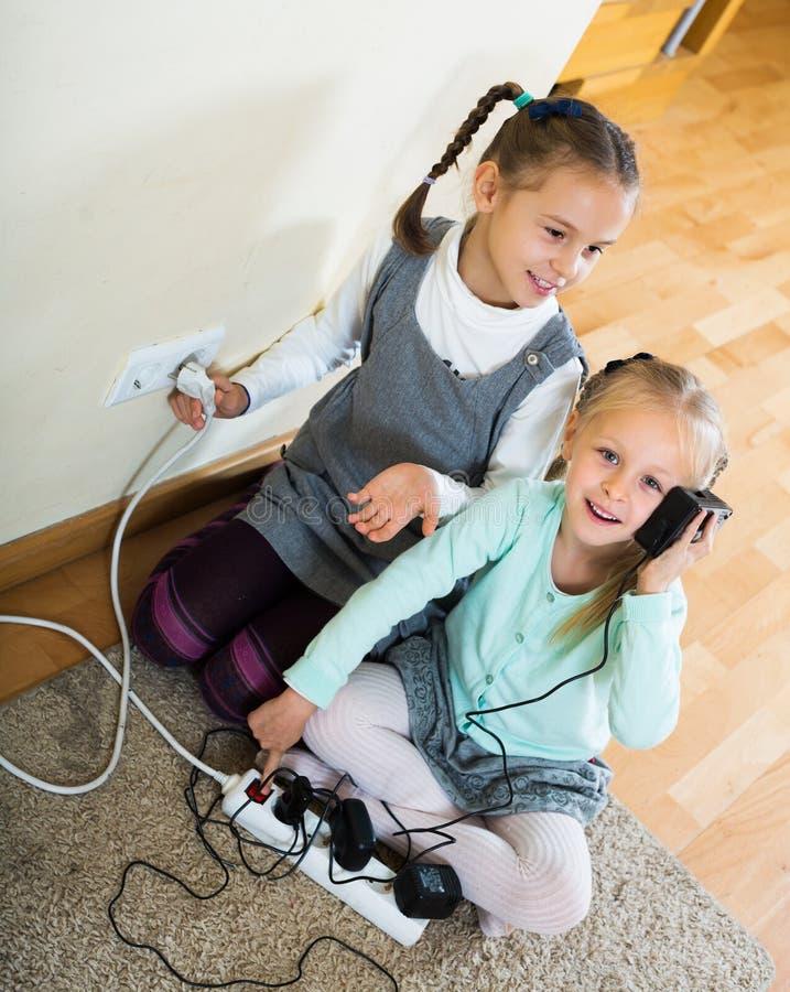 Två flickor som spelar med elektricitet royaltyfri bild
