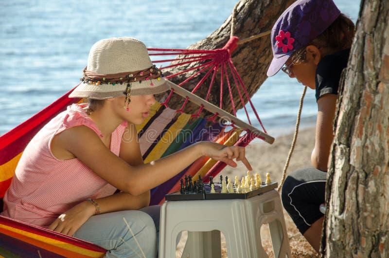 Två flickor som spelar schack vid havet arkivfoton