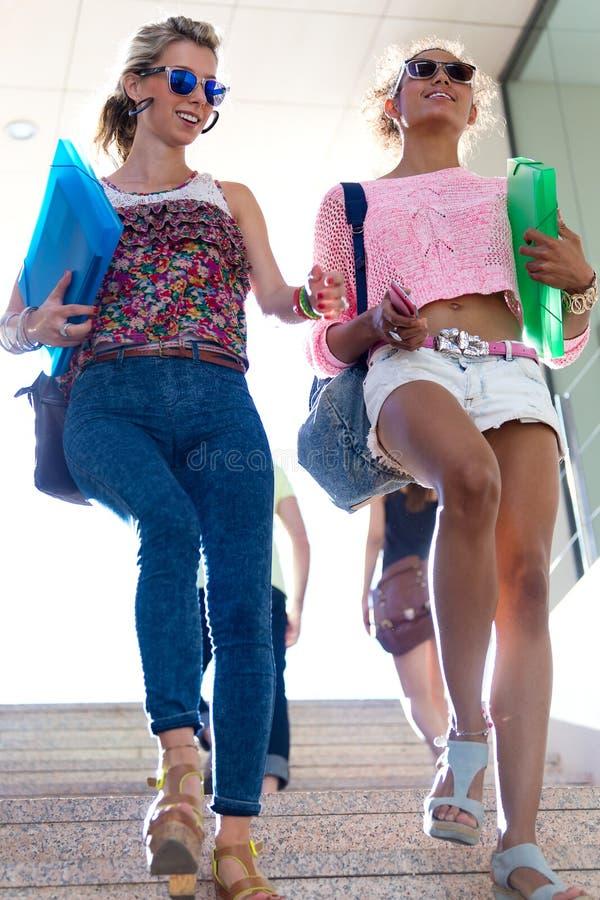 Två flickor som talar och skrattar i trappan royaltyfri bild