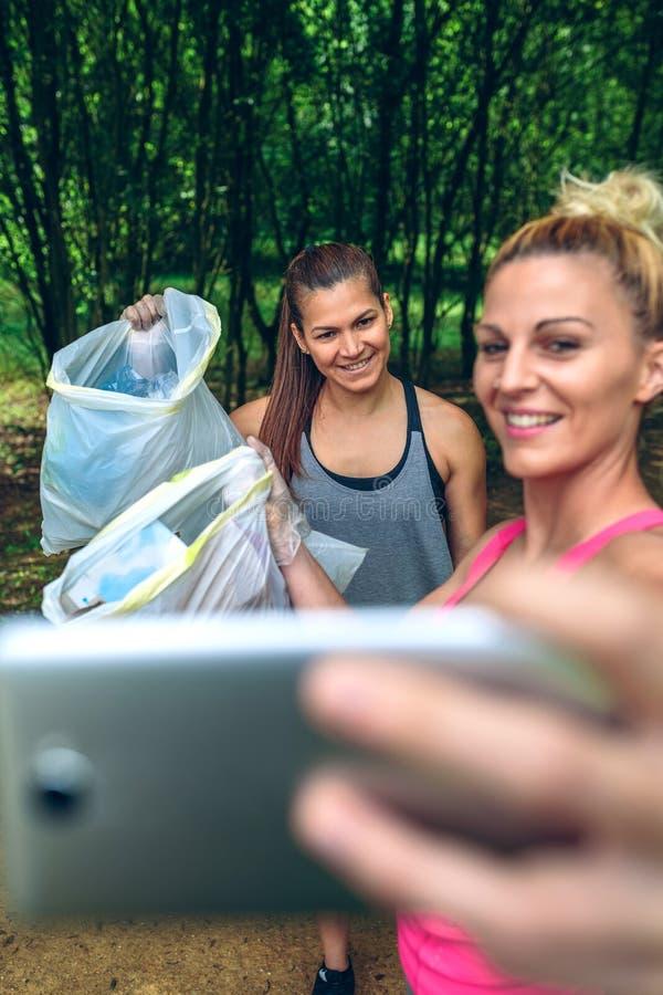 Två flickor som tar en selfie, når plogging royaltyfria bilder
