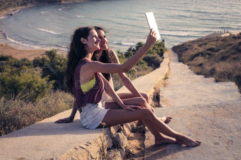 Två flickor som tar en selfie på semester royaltyfria foton