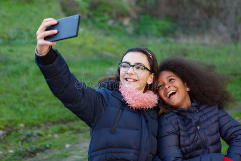 Två flickor som tar ett foto med mobilen arkivfoton