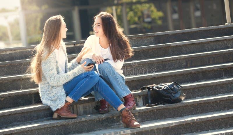 Två flickor som tillsammans talar i gatan arkivbilder