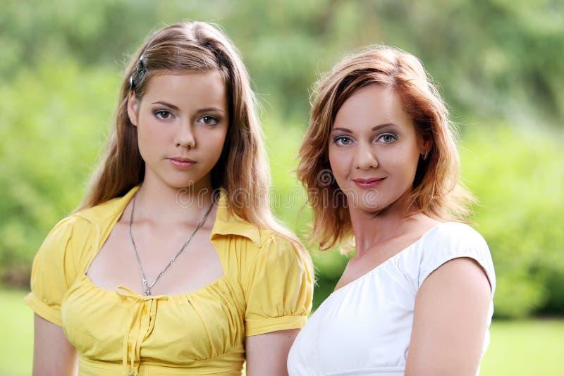 Två flickor som ut hänger i, parkerar royaltyfri foto