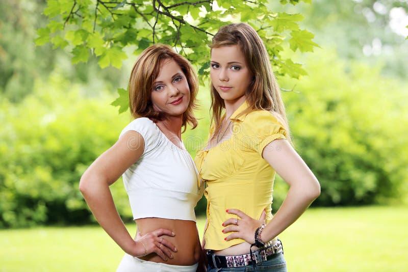 Två flickor som ut hänger i, parkerar royaltyfria bilder