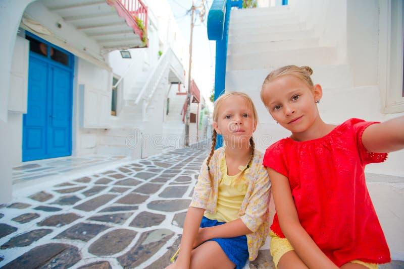 Två flickor som utomhus tar selfiefotoet i grekisk by på den smala gatan arkivbild
