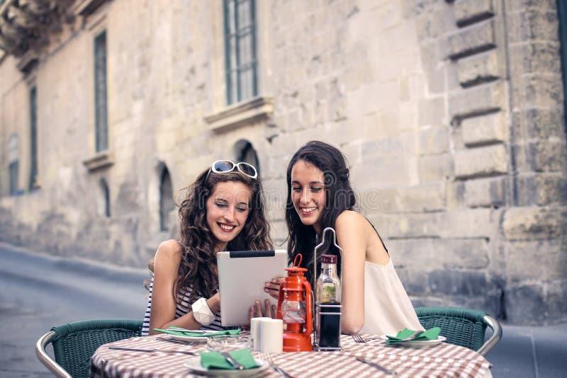 Två flickor som väljer vad för att äta royaltyfri bild