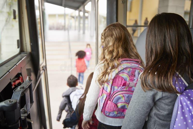 Två flickor som väntar bak deras vänner för att få av skolbussen royaltyfri fotografi
