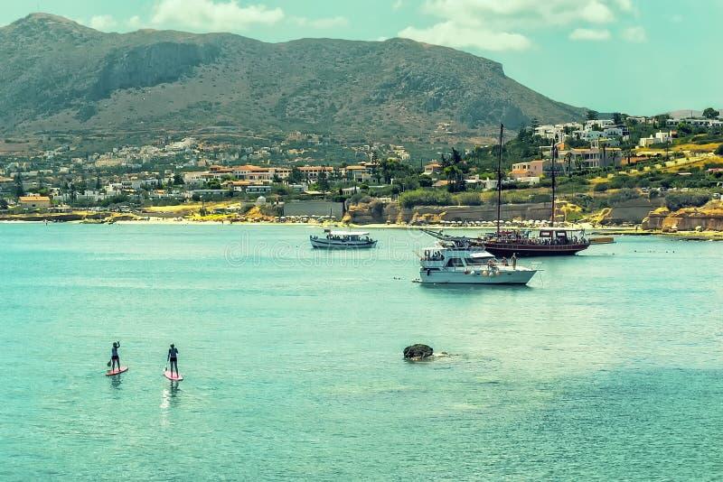 Två flickor står paddla upp i turkosblåttlagun av medelhavet runt om fartyg arkivfoton