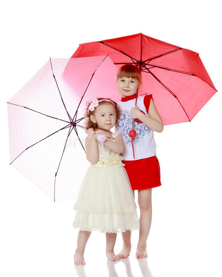 Två flickor står under paraplyer royaltyfria bilder