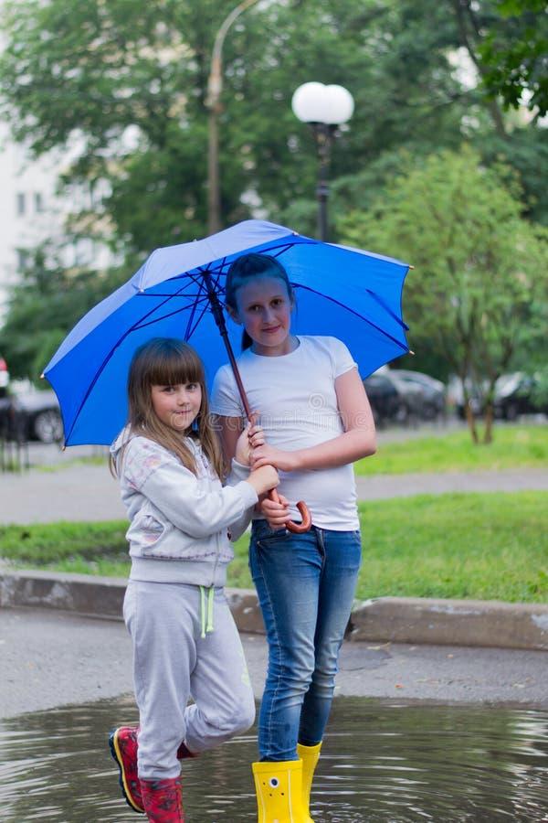 Två flickor under ett paraply royaltyfria bilder