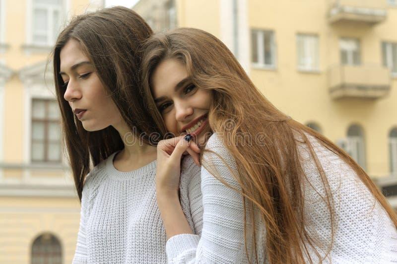 Två flickor vilar och blåser upp bubblor av tuggummi royaltyfri fotografi