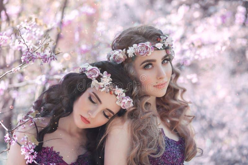 Två flickvänner, en blondin och en brunett, med förälskelse som kramar sig Bakgrund av en härlig blommande lilaträdgård Princen royaltyfria bilder
