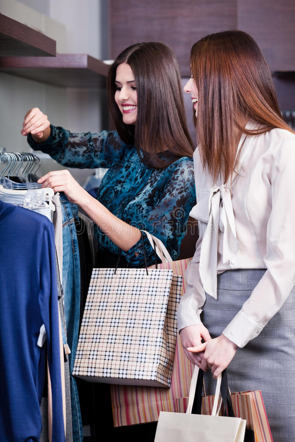 Vänner fingrar kläder som stunder går att shoppa royaltyfria bilder