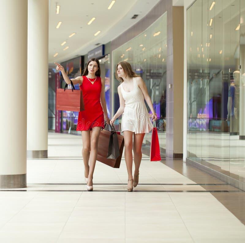 Två flickvänner på shopping går på shoppinggalleria med påsar royaltyfri fotografi