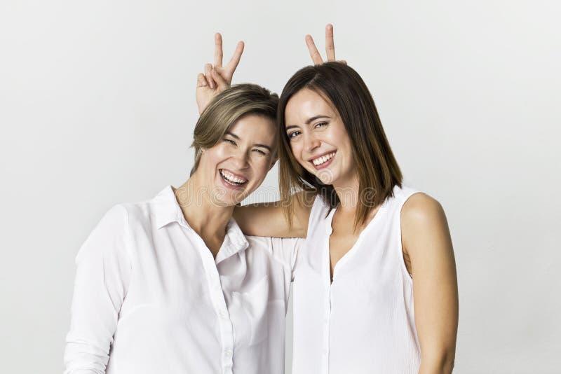 Två flickvänner som har gyckel på studiobakgrund Toothy le stående för två unga kvinnor arkivbild