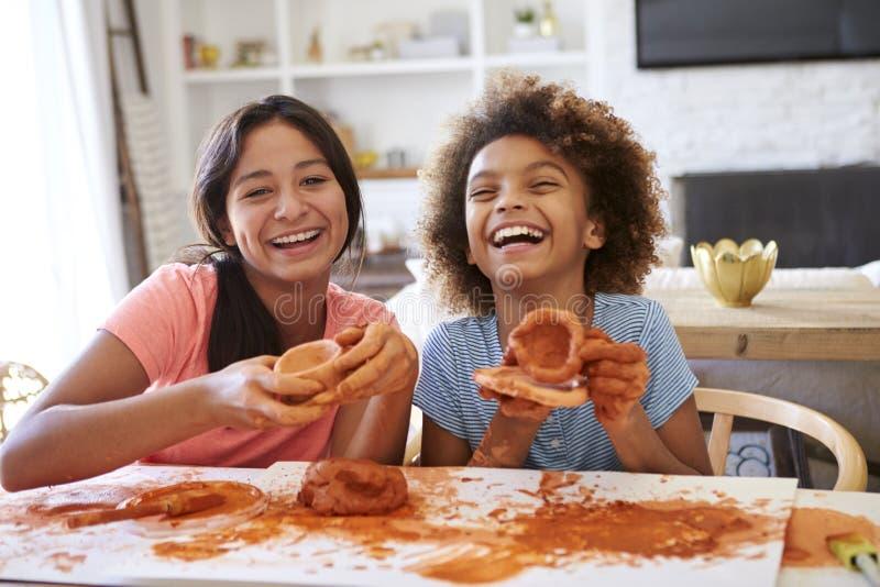 Två flickvänner som har gyckel som spelar med att modellera lera hemma, att skratta och uppvisning av deras skapelser till kamera royaltyfri bild