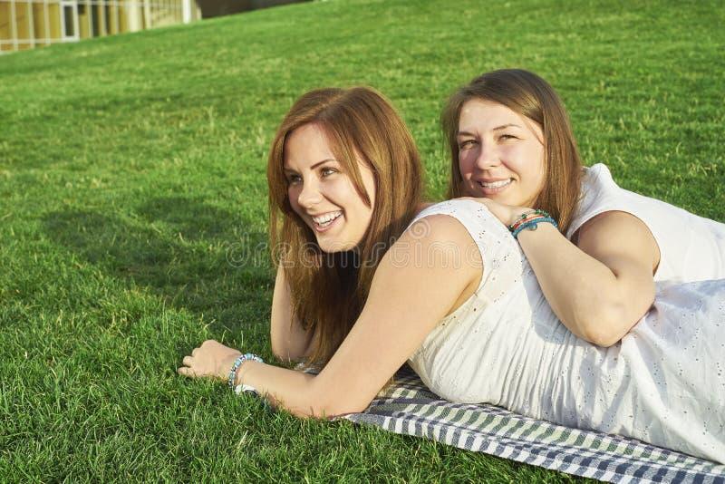 Två flickvänner som ligger på gräsmattan arkivbilder