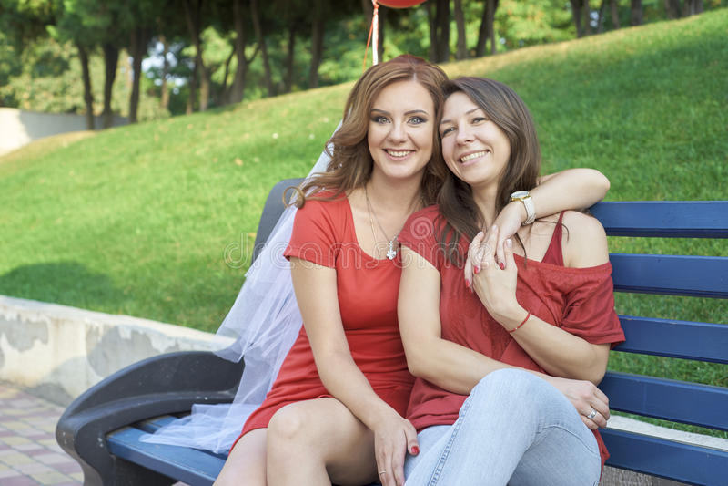 Två flickvänner som sitter på bänken arkivfoton