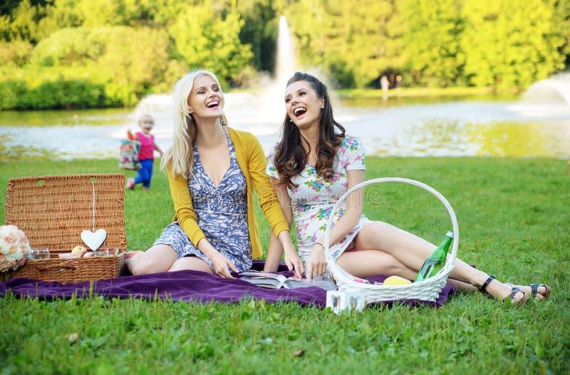 Två flickvänner som skrattar under picknick arkivbilder