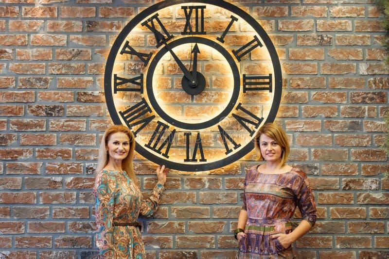 Två flickvänner unga kvinnor står inomhus nära den enorma klockan 5 minuter före midnattshristmas royaltyfri bild