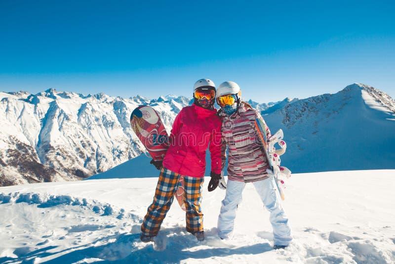 Två flickvänsnowboarders i de alpina bergen arkivbild