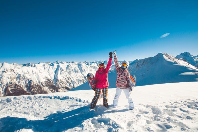Två flickvänsnowboarders i de alpina bergen arkivbilder
