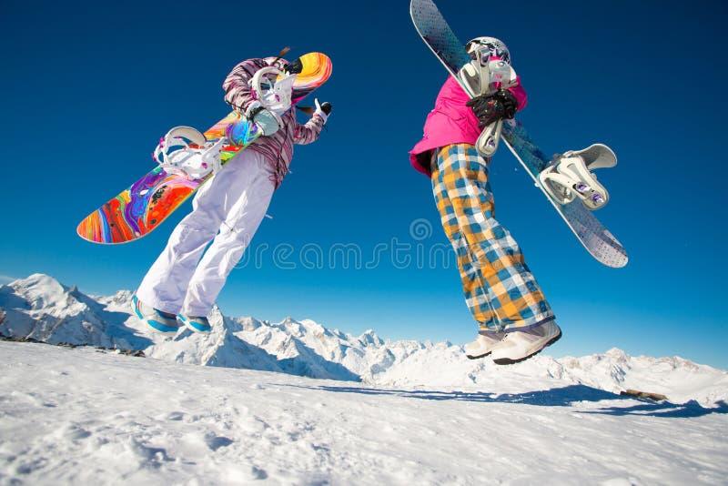 Två flickvänsnowboarders som hoppar i de alpina bergen arkivbild