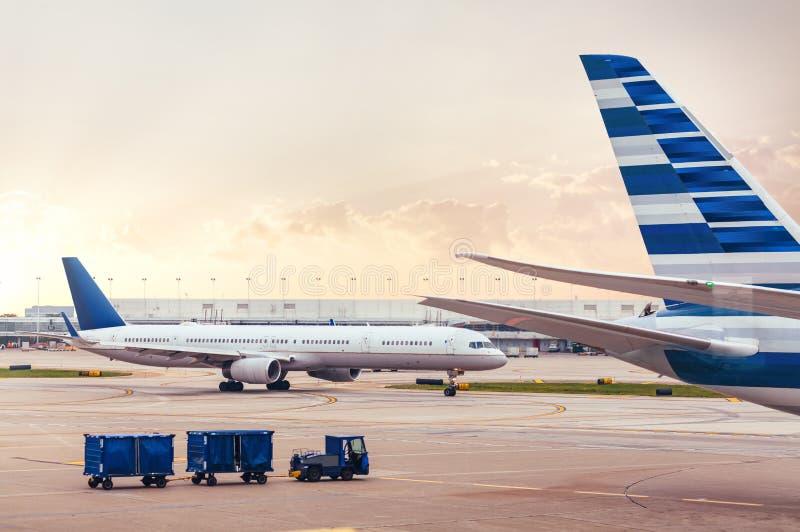 Två flygplan på grov asfaltbeläggning med last på flygplatsen arkivbild